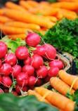 Légumes sur un étal de marché : radis, carottes et aubergines